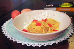 Spaghettone cremoso con carbonara di uova e prosciutto di trota.